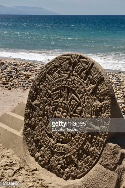 Sand sculpture of an Aztec sundial on the beach at Malecon Puerto Vallarta Mexico