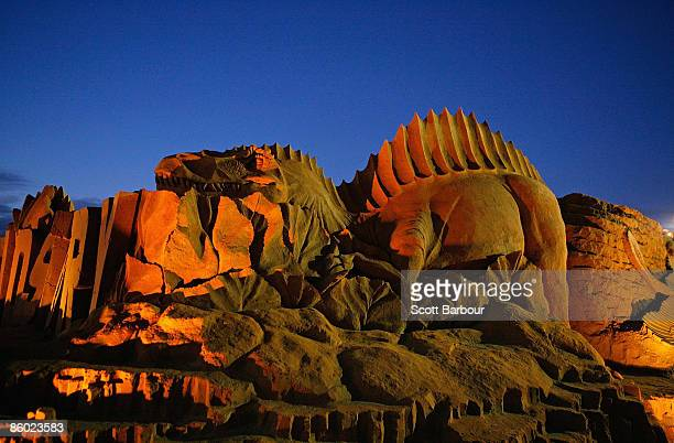 Sand sculptures are illuminated at dusk at 'Dinostory' the theme for this year's annual Sand Sculpting Australia exhibition at Frankston Waterfront...