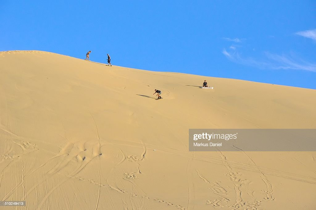 Sand surfing in the dunes near Huacachina, Peru : Stock-Foto