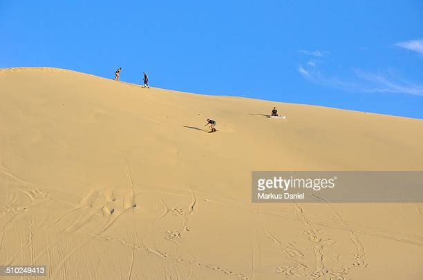 Sand surfing in the dunes near Huacachina, Peru