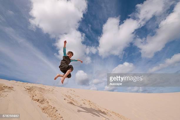 Sand tobogganing down the dunes of the Desert Moreton Island National Park Queensland Australia