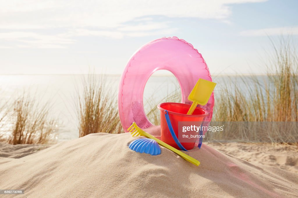 Sand toys and inflatable ring on the beach : Stock Photo