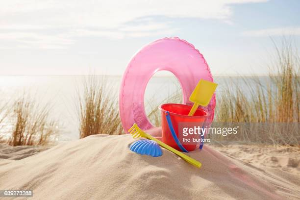 sand toys and inflatable ring on the beach - nature morte photos et images de collection