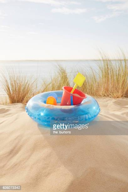 Sand toys and inflatable ring on the beach