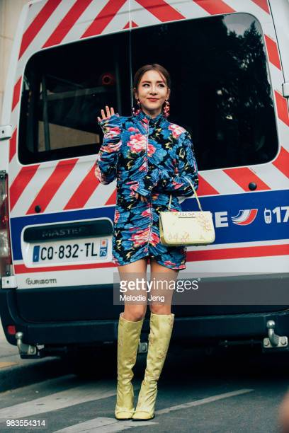 Sandara Park Korean celebrity after the Kenzo show in a short blue floral dress Kenzo bag and yellow jacquard boots during Paris Mens Fashion Week...