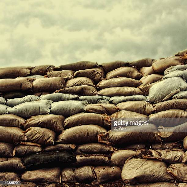 Sandbag levee under stormy sky