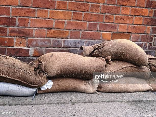 sandbags against brick wall - sandbag stock pictures, royalty-free photos & images