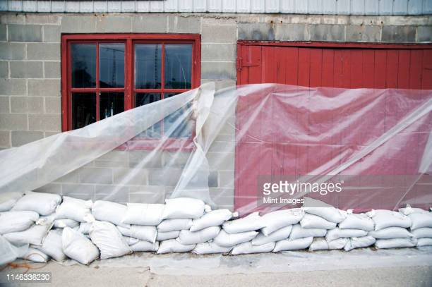 sandbags and glass sheet on building wall - sandbag stock pictures, royalty-free photos & images