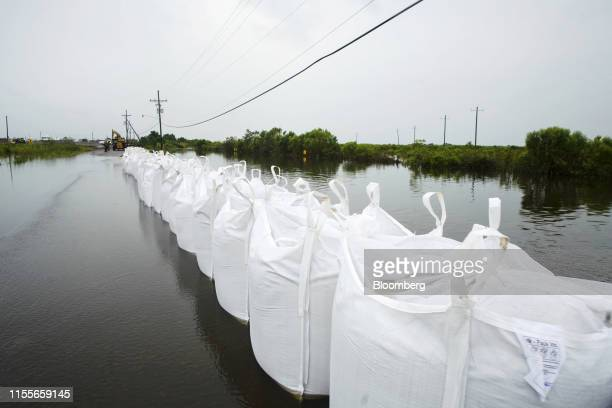 Sandbags line a flooded road following a levee breach after Tropical Storm Barry made landfall in Myrtle Grove, Louisiana, U.S., on Sunday, July 14,...
