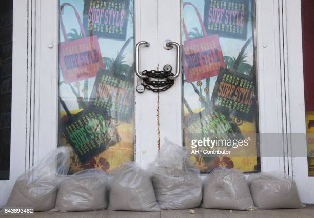 Sandbags sit at a doorway to a boardedup store following mandatory evacuation orders in Miami Beach Florida September 7 ahead of Hurricane Irma...