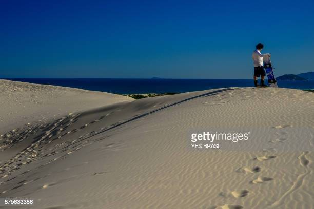 Sandboarder appreciates Joaquina's dunes