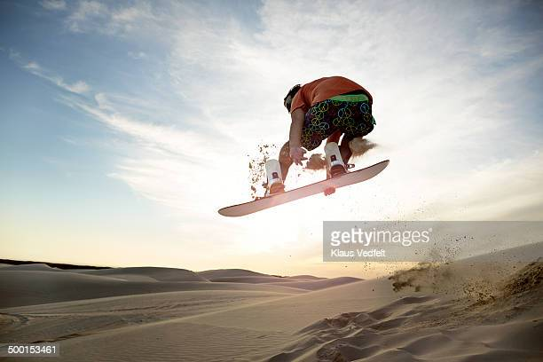 Sandboarder doing front side grab in the air