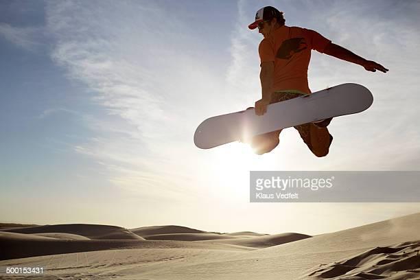 Sandboarder doing 'Method' grab in the air
