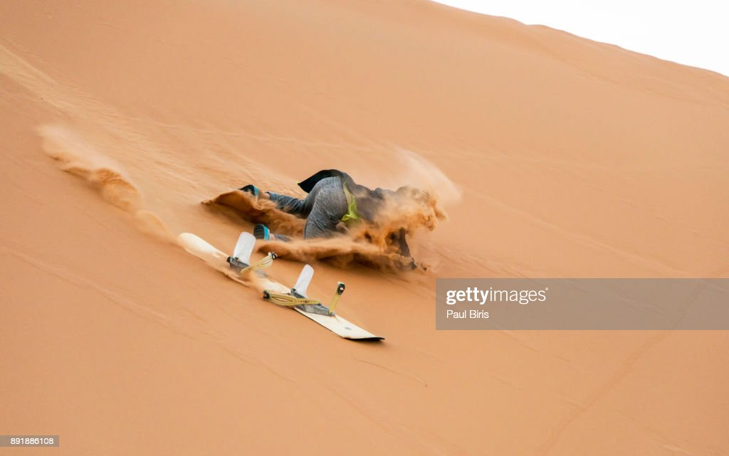 Sand-boarding the Saharan sand dunes, Merzouga, Morocco : Stock Photo