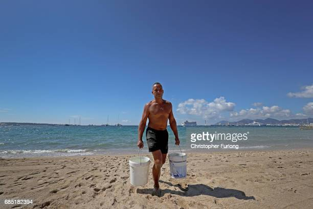 A sandcastle artist fetches sea water on the beach of the Boulevard de la Croisette during the Cannes Film Festival on May 19 2017 in Cannes France...