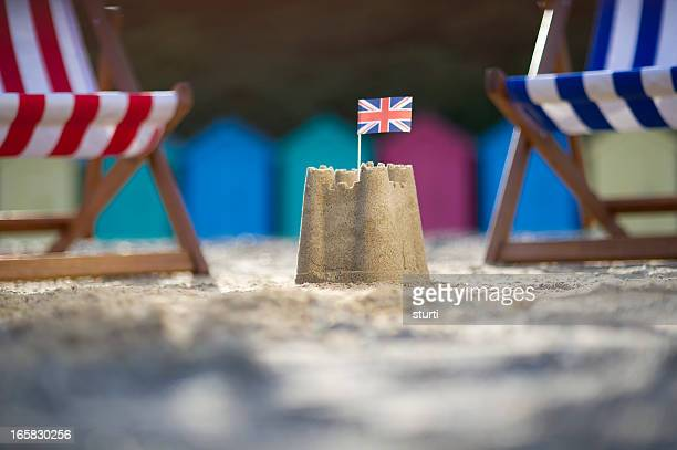 Sandcastle with UK flag between two deck chairs