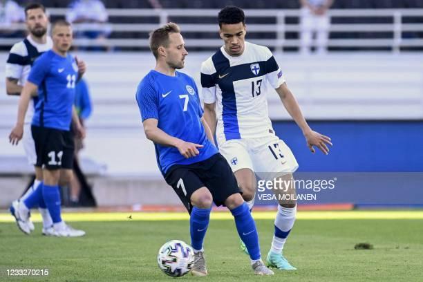 Sander Puri of Estonia and Finland's midfielder Pyry Soiri vie for the ball during the friendly football match Finalnd v Estonia in Helsinki on June...