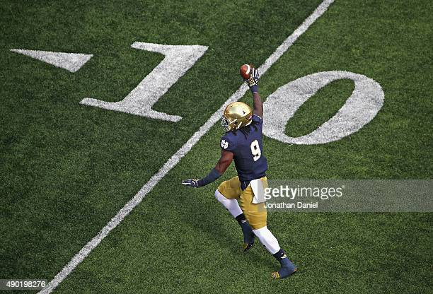 Sanders of the Notre Dame Fighting Irish holds up the ball as he races towards the end zone against the Massachusetts Minutemen at Notre Dame Stadium...
