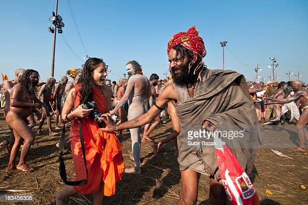 CONTENT] A sandhu and a female devotee walk in procession to bathe on the banks of Sangam the confluence of the holy rivers Ganges Yamuna and the...