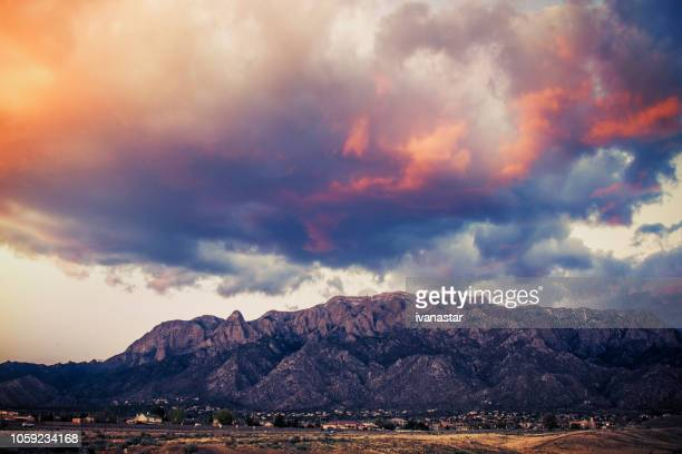 sandia mountains with majestic sky and clouds at sunset - sandia mountains stock photos and pictures