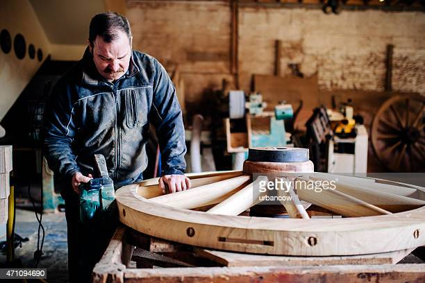 Sanding the outer rim, wooden cartwheel, skilled Wheelwright