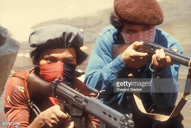 Sandinistas aiming rifles behind a barricade.