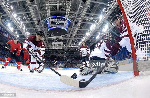 Sandis Ozolins and Arturs Kulda of Latvia stop a shot behind Mathias Seger in the second period against Switzerland during the Men's Ice Hockey...