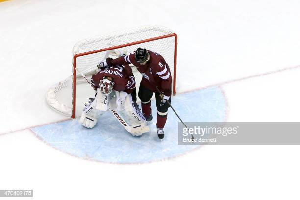 Sandis Ozolins of Latvia and Kristers Gudlevskis of Latvia react during the Men's Ice Hockey Quarterfinal Playoff against Canada on Day 12 of the...