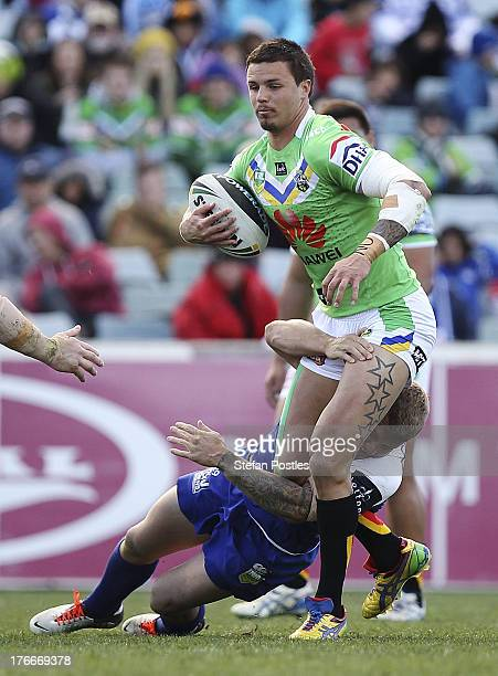 Sandor Earl of the Raiders is tackled during the round 23 NRL match between the Canberra Raiders and the Canterbury Bulldogs at Canberra Stadium on...
