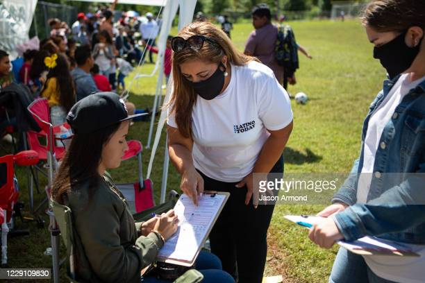 Sandra Amado Gomez and her daughter Aylen Agostina Gomez registers a woman to vote during halftime at the championship game of soccer on Sunday,...