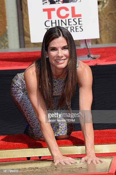 Sandra Bullock poses for a photo as she is immortalized with a hand and footprint ceremony at TCL Chinese Theatre on September 25 2013 in Hollywood...