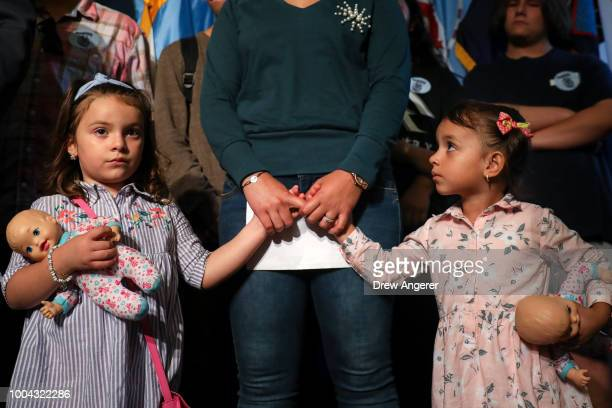 Sandra Chica, wife of Pablo Villavicencio, holds the hands of her children Luciana and Antonia during an advocacy rally and press conference in...