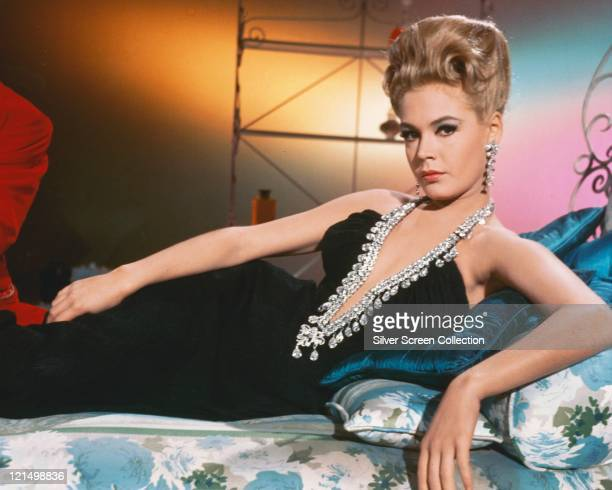 Sandra Dee US actress wearing a black halterneck dress with a beaded plunging neckline with her hair in a beehive hairstyle reclining on a bed circa...