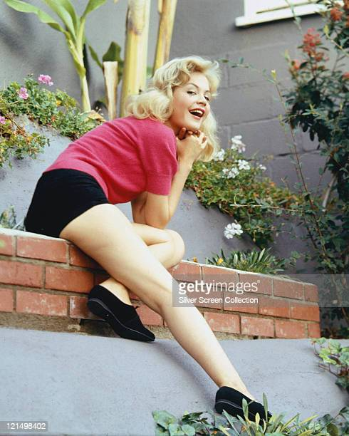Sandra Dee US actress wearing a pink shortsleeved blouse and black knickers posing on a brick wall with her right leg extended down circa 1965