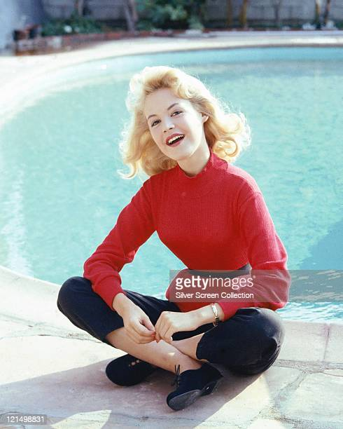 Sandra Dee US actress wearing a red jumper tied at the waist with a black belt and dark blue trousers as she sits crosslegged at the edge of a...