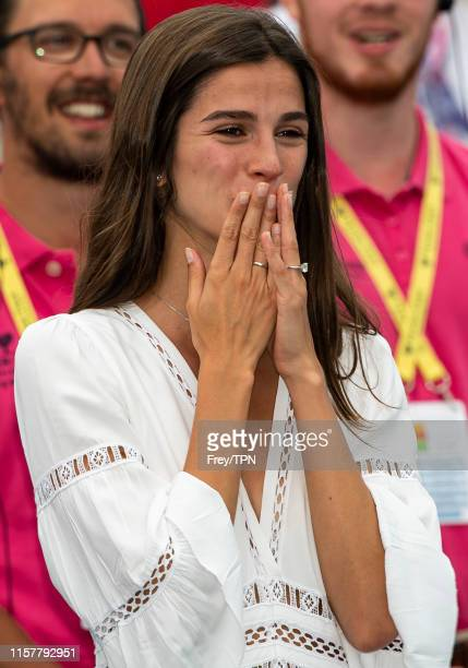 Sandra Gago, fiancee of Feliciano Lopez of Spain, watches him pose with the trophy after his victory over Gilles Simon of France in the final of the...