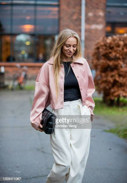 Sandra Hagelstam seen wearing pink cropped jacket, black Bottaga bag, white pants outside Baum und Pferdgarten during Copenhagen Fashion Week...