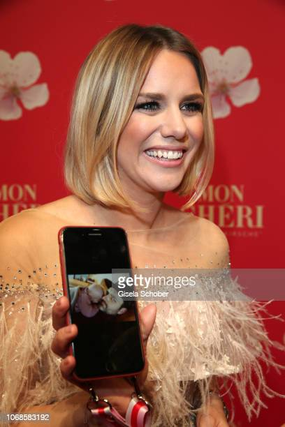 Sandra Kuhn shows her baby and partner on her mobile phone during the Mon Cheri Barbara Tag at Alte Bayerische Staatsbank on December 4 2018 in...