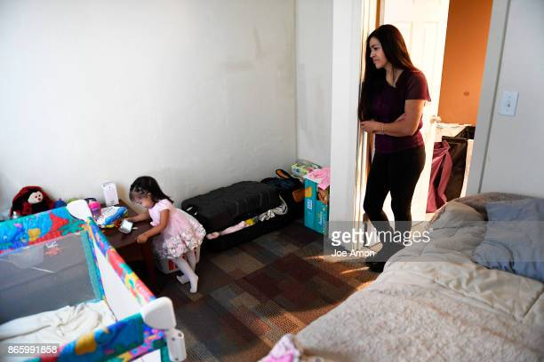 Sandra Lopez watching her daughter Areli GonzalezLopez almost 2 watching cartoons on her phone in the bed room they share in the basement of the...