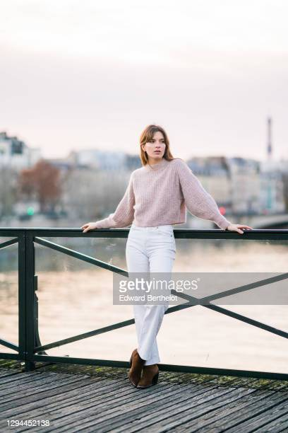 Sandra Maurel wears a pale pink wool pullover, white denim jeans pants, brown pointy suede boots, on December 20, 2020 in Paris, France.