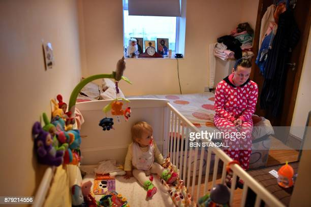 Sandra Rumkiene poses sitting with her young daughter Jessica in their bedroom in Connect House sheltered housing in Mitcham south west London, on...