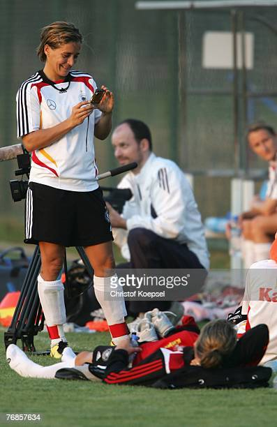 Sandra Smisek makes a picture of Simone Laudehr during the Women's German National Team training session on the training ground at the Wuhan Sports...