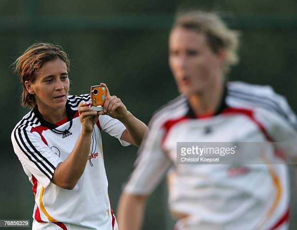 Sandra Smisek makes pictures of Anja Mittag during the Women's German National Team training session on the training ground at the Wuhan Sports...