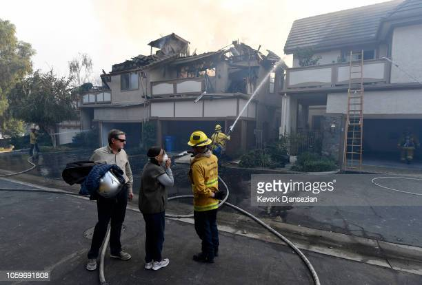 Sandro and Antoinette Zanon survey the damage with a Los Angeles City firefighter as their neighbor homes burns down by Woolsey fire on November 9,...