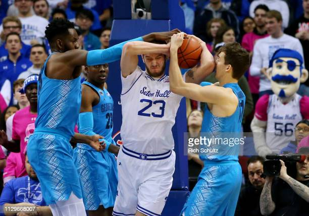 Sandro Mamukelashvili of the Seton Hall Pirates attempts to hold onto the ball as Jessie Govan and Greg Malinowski of the Georgetown Hoyas defend...