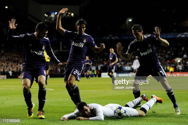 Sandro of Spurs lies on the ground as Raul Albiol Mesut Ozil and Alvaro Arbeloa of Real Madrid react during the UEFA Champions League quarter final...
