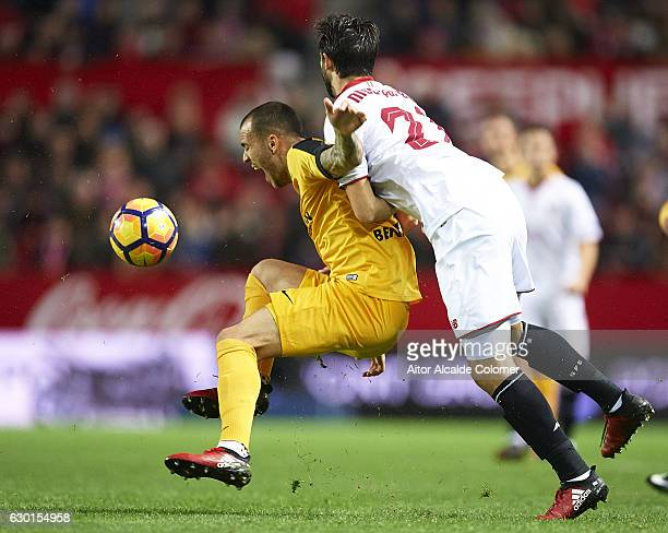 Sandro Ramirez of Malaga CF being fouled by Nicolas Pareja of Sevilla FC during the La Liga match between Sevilla FC and Malaga CF at Estadio Ramon...