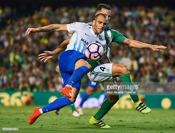 Sandro Ramirez of Malaga CF competes for the ball with Bruno Gonzalez of Real Betis Balompie during the match between Real Betis Balompie vs Malaga...