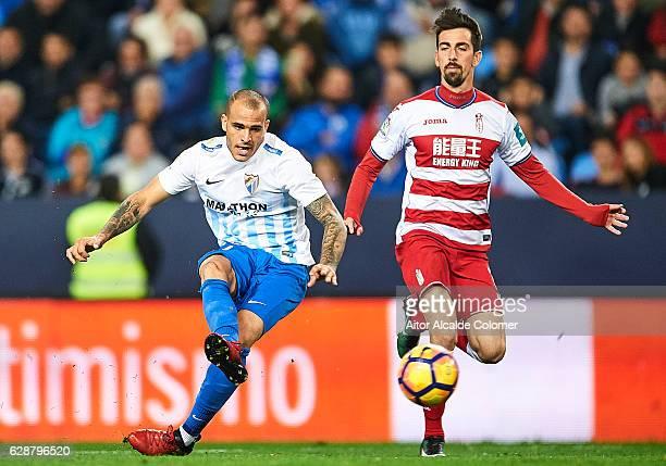 Sandro Ramirez of Malaga CF shoots while is being followed by Isaac Cuenca of Granada CF during La Liga match between Malaga CF and Granada CF at La...