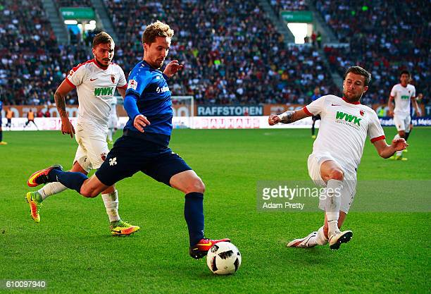 Sandro Sirigu of SV Darmstadt 98 is challenged by Daniel Baier of Augsburg during the Bundesliga match between FC Augsburg and SV Darmstadt 98 at WWK...